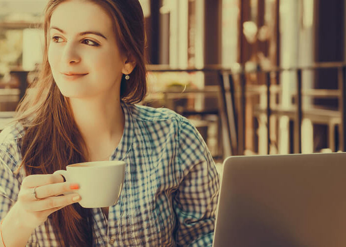 woman on vacation, working on laptop drinking coffee